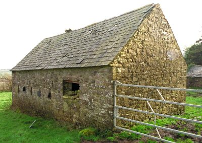An old stone barn with a slate roof.
